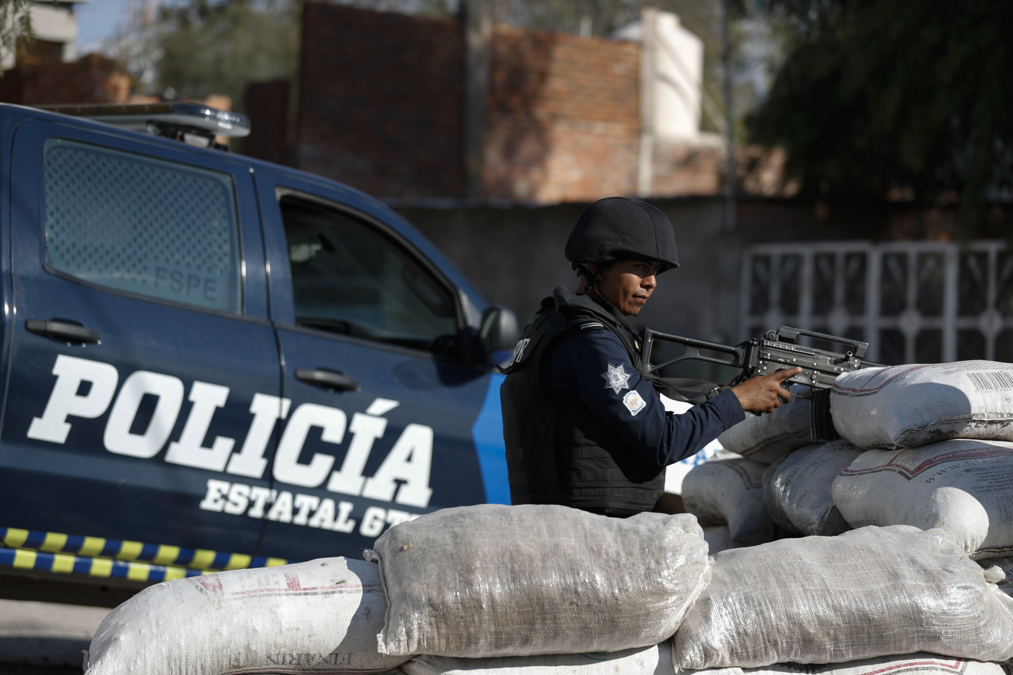 Police stand guard behind a parapet of sandbags at the entrance to Santa Rosa de Lima, birthplace of a local cartel that goes by the same name, in Guanajuato state, Mexico, in February. Mexico's fastest-rising cartel, the Jalisco New Generation gang, has a reputation for ruthlessness and violence unlike any since the fall of the old Zetas cartel. | AP
