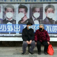 A man and woman sit in front of a poster reminding citizens to wear face masks as a preventive measure against the COVID-19 coronavirus, at a bus stop in Bozhou, in China's eastern Anhui province, on Friday. | AFP-JIJI