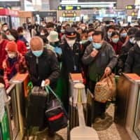 People wearing face masks as a preventive measure against the COVID-19 novel coronavirus walk to a train, one of the stops being Wuhan, at a station in Shanghai on Saturday.   AFP-JIJI
