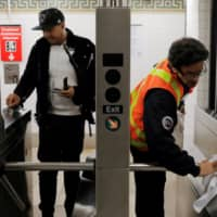 An MTA worker wipes down a turnstile at the Broad Street subway station after more cases of coronavirus were confirmed in New York City on Tuesday. | REUTERS
