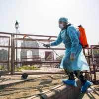 A security staffer sprays disinfectant near the India Gate monument, temporary closed due to the coronavirus, in New Delhi, on Sunday. | BLOOMBERG