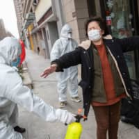 A woman who has recovered from the COVID-19 coronavirus infection is disinfected by volunteers as she arrives at a hotel for a 14-day quarantine after being discharged from a hospital in Wuhan, in China's central Hubei province, on Sunday.   AFP-JIJI
