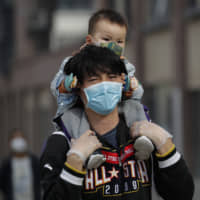 A man carries a toddler on his shoulders as both wear protective face masks in Beijing on Wednesday. | AP