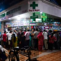 People gather at a pharmacy to buy supplies following the announcement of a government-imposed nationwide lockdown in Mumbai on Tuesday. | AFP-JIJI