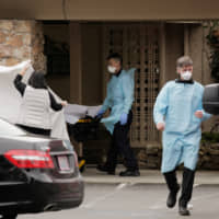 A patient is transferred to an ambulance at the Life Care Center of Kirkland, a long-term care facility linked to two of the three confirmed coronavirus cases in Washington state, in the Seattle suburb of Kirkland on Sunday. | REUTERS
