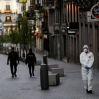 A medical worker in a protective suit walks past police officers patrolling a deserted street during the coronavirus outbreak in Madrid on Sunday. | REUTERS