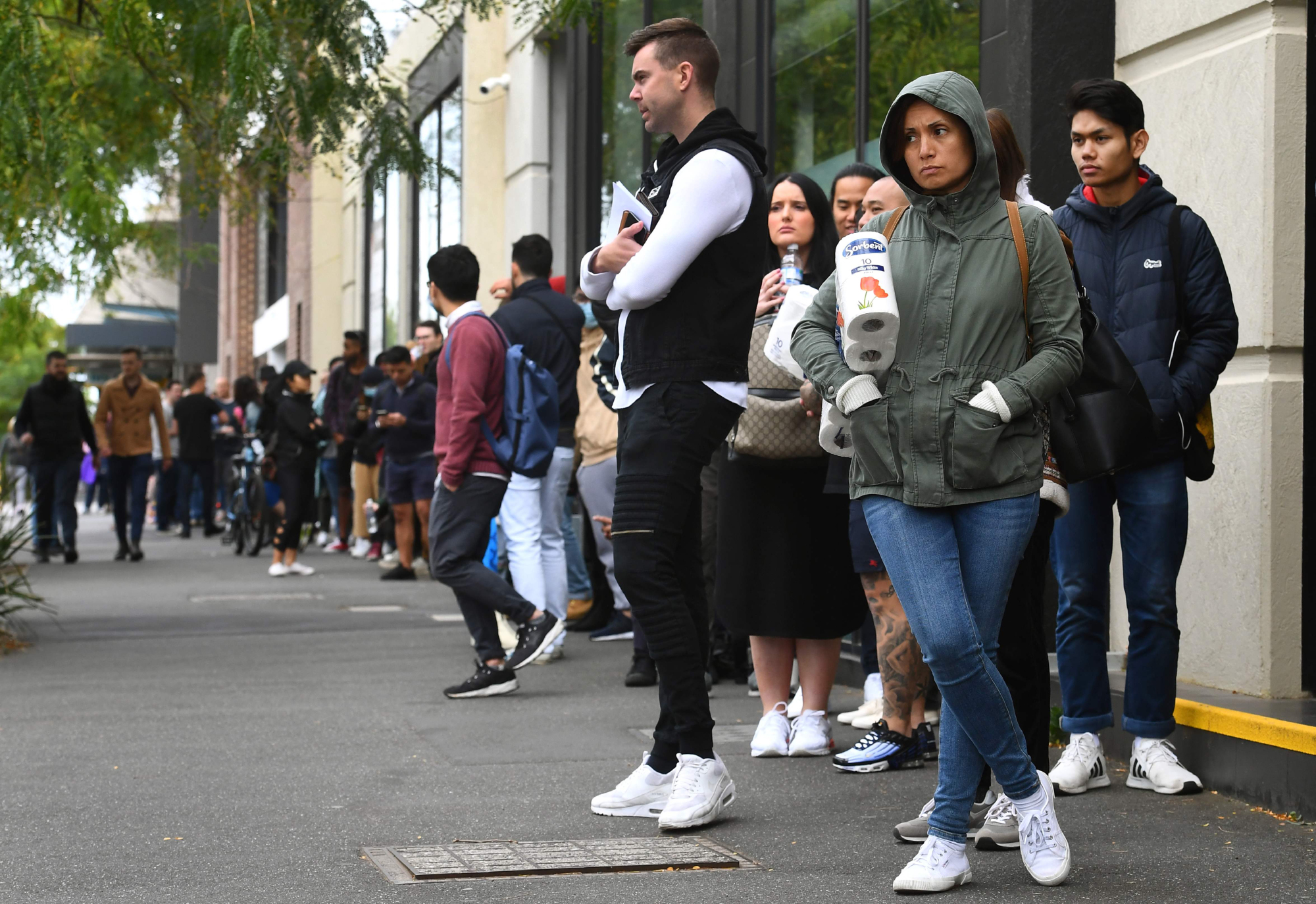 Hundreds of people line up outside a Centrelink government welfare center in Melbourne on March 23, when the forced closure of pubs, casinos, churches and gyms began across Australia. | AFP-JIJI