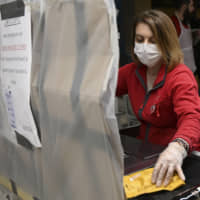 A cashier behind a protective plastic tarp works in a supermarket in Strasbourg on Thursday after a strict lockdown came into effect in France to stop the spread of the virus that causes the disease COVID-19. | AFP-JIJI