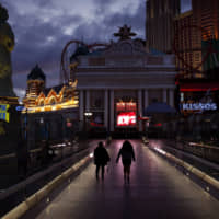 People walk Wednesday along the Las Vegas Strip, devoid of the usual crowds after casinos were ordered to shut down due to the coronavirus outbreak. | AP