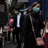 People wear protective face masks as they walk through a market in Hong Kong's financial district amid the outbreak of COVID-19. | REUTERS