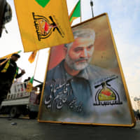 Members of the Kataib Hezbollah militia in Iraq hold a picture of Iranian Quds Force commander Maj. Gen. Qassem Soleimani in Baghdad on Jan. 4, ahead of the funeral of militia commander Abu Mahdi al-Muhandis, who was killed along with Soleimani in an airstrike at Baghdad's main airport. | REUTERS