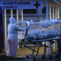 A patient in a biocontainment unit is carried on a stretcher at the Columbus Covid 2 Hospital in Rome on Monday. | AP
