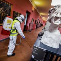 A worker sprays disinfectant as sanitization operations against the new coronavirus are carried out in the museum hosted by the Maschio Angioino medieval castle in Naples, Italy, on March 10. | AP