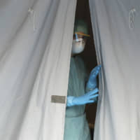 A medical staffer watches from a tent Thursday at one of the emergency structures that were set up to ease procedures at the Brescia hospital in northern Italy. | AP