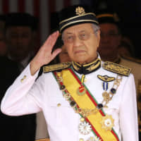 Mahathir Mohamad, then Malaysia's prime minister, salutes during the opening of the 14th parliament session in Kuala Lumpur in 2018. Mahathir abruptly resigned last Monday. | AP