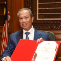 Malaysian Prime Minister Muhyiddin Yassin poses after signing a document on his first day in office in Putrajaya on March 2. | AFP-JIJI