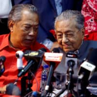 Mahathir Mohamad (right) listens to Muhyiddin Yassin during a news conference in April 2018, when both were allies. | REUTERS