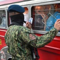 A Philippine policeman inspects identification of jeepney passengers at a checkpoint bordering nearby Cavite province and suburban Las Pinas in Manila on Sunday as the government steps up efforts to curb the spread of the new coronavirus. | AFP-JIJI