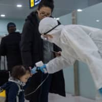 A child has her temperature taken as foreign diplomats and embassy staff prepare to board a flight to Vladivostok at Pyongyang International Airport on Monday. | AFP-JIJI
