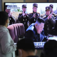 A broadcast at Seoul Station shows North Korean leader Kim Jong Un overseeing tests of short-range ballistic missiles last weekend. Photos released by Pyongyang showed military personnel without face masks for the first time since late February. | AP