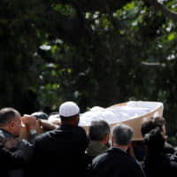 The body of a victim of the mosque attacks is carried during a burial ceremony at the Memorial Park Cemetery in Christchurch, New Zealand, on March 20, 2019. | REUTERS