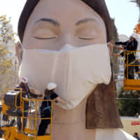 Workers place a mask on a figure representing the Fallas festival in Valencia, Spain, on Wednesday. The festival, which was due to take place on Friday, has been cancelled over the coronavirus outbreak. | AP