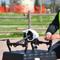 A police officer demonstrates the monitoring of citizens' movements with a drone in Grosseto, Italy, on March 20. | AP