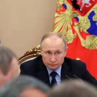 Russian President Vladimir Putin chairs a meeting at the Kremlin in Moscow on Tuesday. | VIA REUTERS