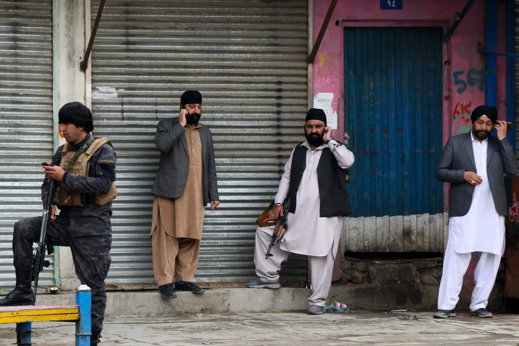 An Afghan security personnel stands along with Sikhs near the site of an attack to a Sikh temple in Kabul on Wednesday. | AFP-JIJI