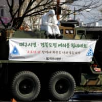 A soldier sits atop a military vehicle for quarantine work at a screening facility for coronavirus patients in Daegu, South Korea, on Sunday. | REUTERS