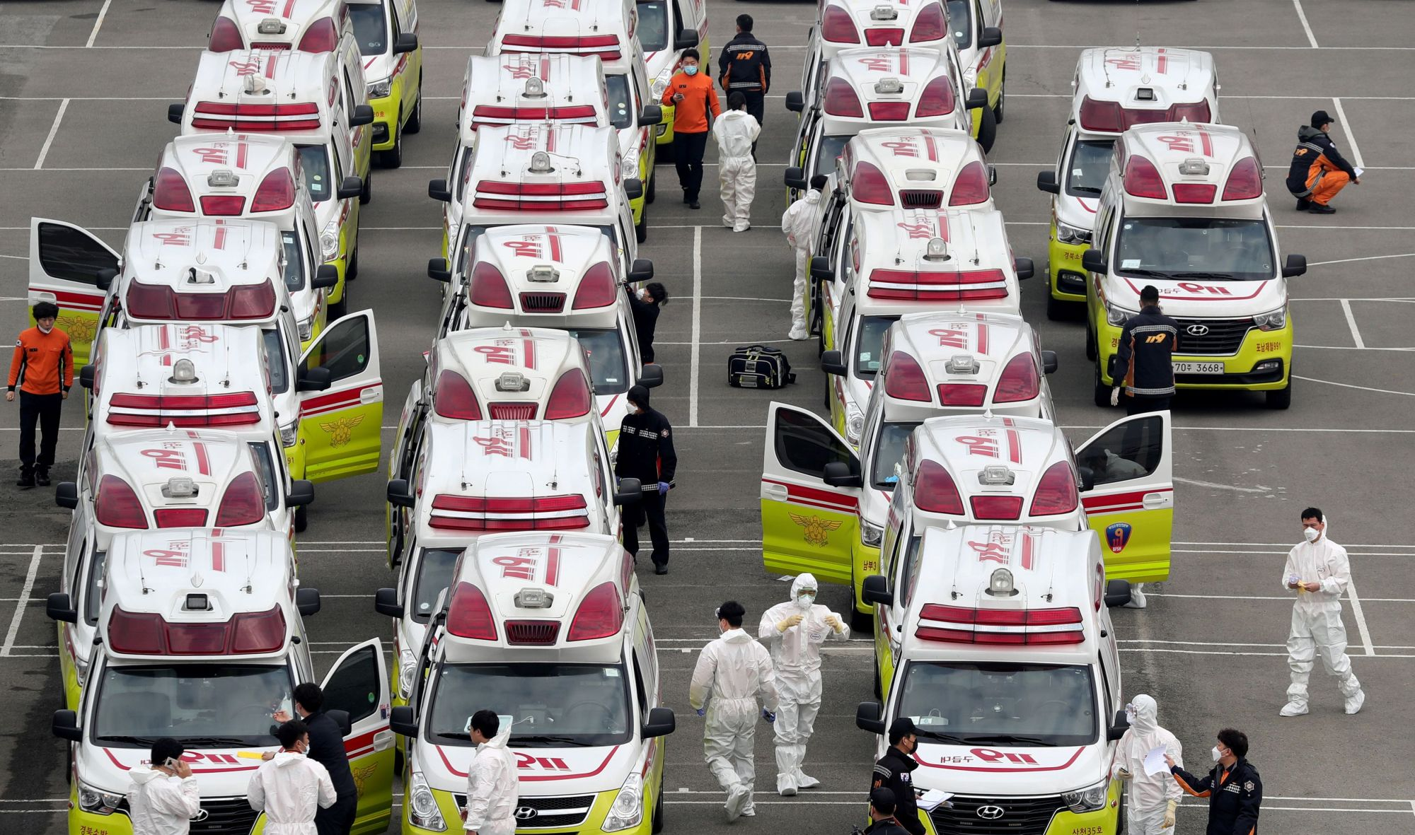 Ambulances to transport patients infected with the new coronavirus are parked in Daegu, South Korea, on Sunday.   YONHAP / VIA REUTERS