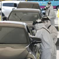Medical members wearing protective gear take samples from a driver with suspected symptoms of the COVID-19 coronavirus, at a 'drive-thru' virus test facility in Goyang, north of Seoul, on Saturday. | AFP-JIJI