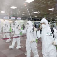 South Korean soldiers wearing protective gear spray disinfectant to help prevent the spread of the COVID-19 coronavirus, at Daegu International Airport in Daegu on Friday. | YONHAP / VIA AFP-JIJI