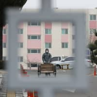 A South Korean health official wearing protective gear walks inside a closed apartment complex after 46 residents were confirmed to have the COVID-19 coronavirus, in Daegu on Saturday. | YONHAP / VIA AFP-JIJI