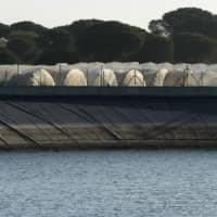 Greenhouses stand beside a reservoir, in Lucena del Puerto, Spain, on March 5. | AFP-JIJI