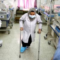 A nurse with a broken leg works in a room where premature babies are cared for in incubators at a maternity hospital in Idlib on Feb. 27.   REUTERS