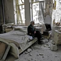 A 70-year-old Syrian man smokes his pipe as he sits in his destroyed bedroom listening to music in Aleppo's formerly rebel-held al-Shaar neighborhood in March 2017. | AFP-JIJI