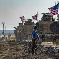 A Syrian boy on his bicycle watches as a convoy of U.S. armored vehicles patrols near the northeastern town of Qahtaniyah near the border with Turkey on Oct. 31. | AFP-JIJI
