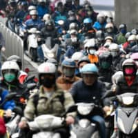 Motorcyclists wearing face masks to prevent the infections of the COVID-19 coronavirus, ride during the peak hours while heading to work in Taipei on Wednesday. Taiwan plans to bar all new arrivals by foreign nationals, adding to the growing ranks of governments shutting their borders in a bid to slow the global spread of the coronavirus. | AFP-JIJI