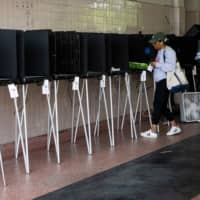 A woman casts her vote during the Florida primary election in Miami on Tuesday. | AFP-JIJI