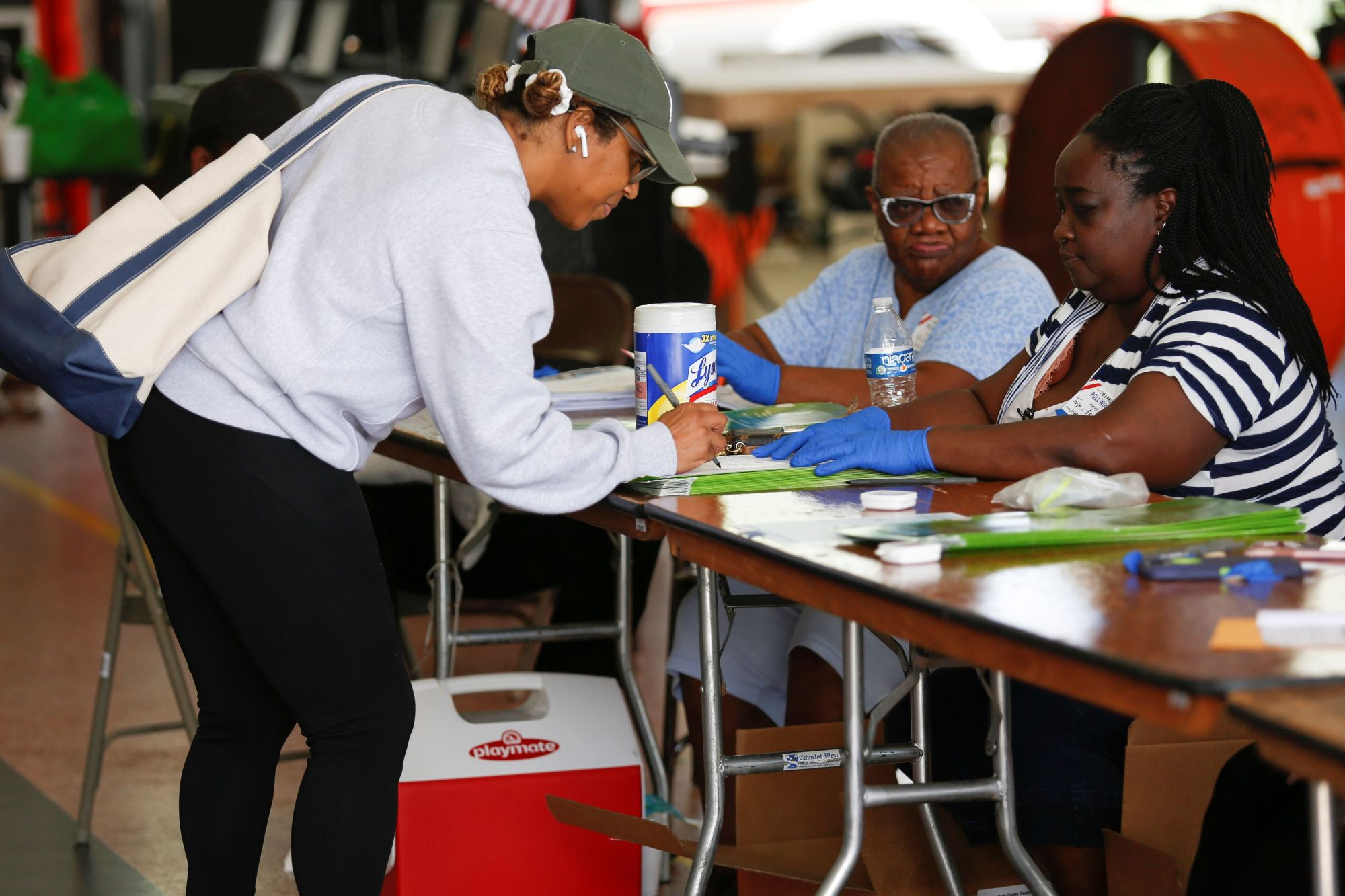 A voter signs her ballot before casting her vote at a polling center during the Democratic presidential primary election in Miami on Tuesday. | REUTERS