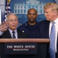 U.S. President Donald Trump listens as Director of the National Institute of Allergy and Infectious Diseases Anthony Fauci, a member of the coronavirus (COVID-19) task force, answers a question about the virus and the current outbreak during a news briefing at the White House on Monday. | REUTERS