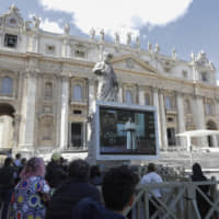 Worshippers watch Pope Francis deliver the Angelus prayer on a giant screen to avoid crowds in St. Peter's Square at the Vatican on Sunday. | AP