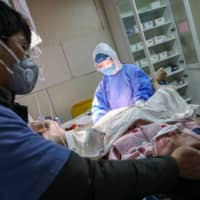 A woman wearing a protective face mask gives birth at a hospital in Wuhan on Feb. 23. | AFP-JIJI
