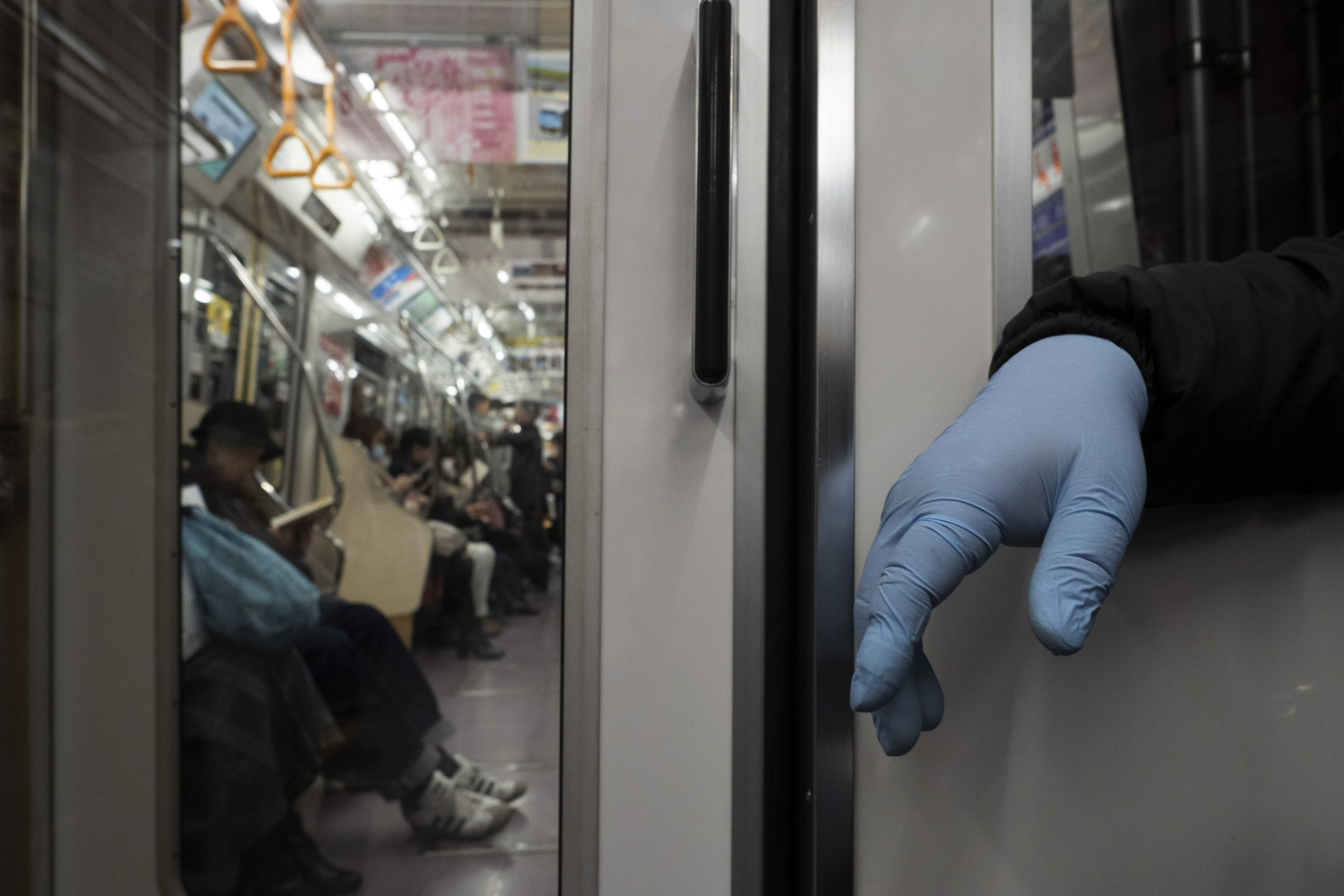 A man wearing a protective glove sits in a train in Tokyo on Monday. The novel coronavirus can survive on surfaces or in the air for several hours, according to a U.S.-government funded study published Tuesday. | AP