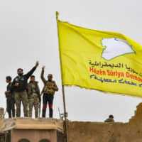 Fighters of the Syrian Democratic Forces flash the victory sign next to their unfurled flag in the village of Baghouz in Syria's eastern Deir Ezzor province on March 24, 2019, after the Islamic State group's 'caliphate' was declared defeated. | AFP-JIJI