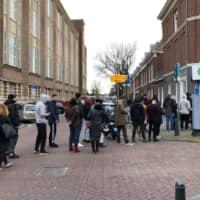 People queue outside a cannabis coffee shop in the Hague on Sunday, after the Dutch government ordered the closing of all schools, bars, restaurants, sex clubs and cannabis cafes in a bid to fight the spread of COVID-19. | AFP-JIJI