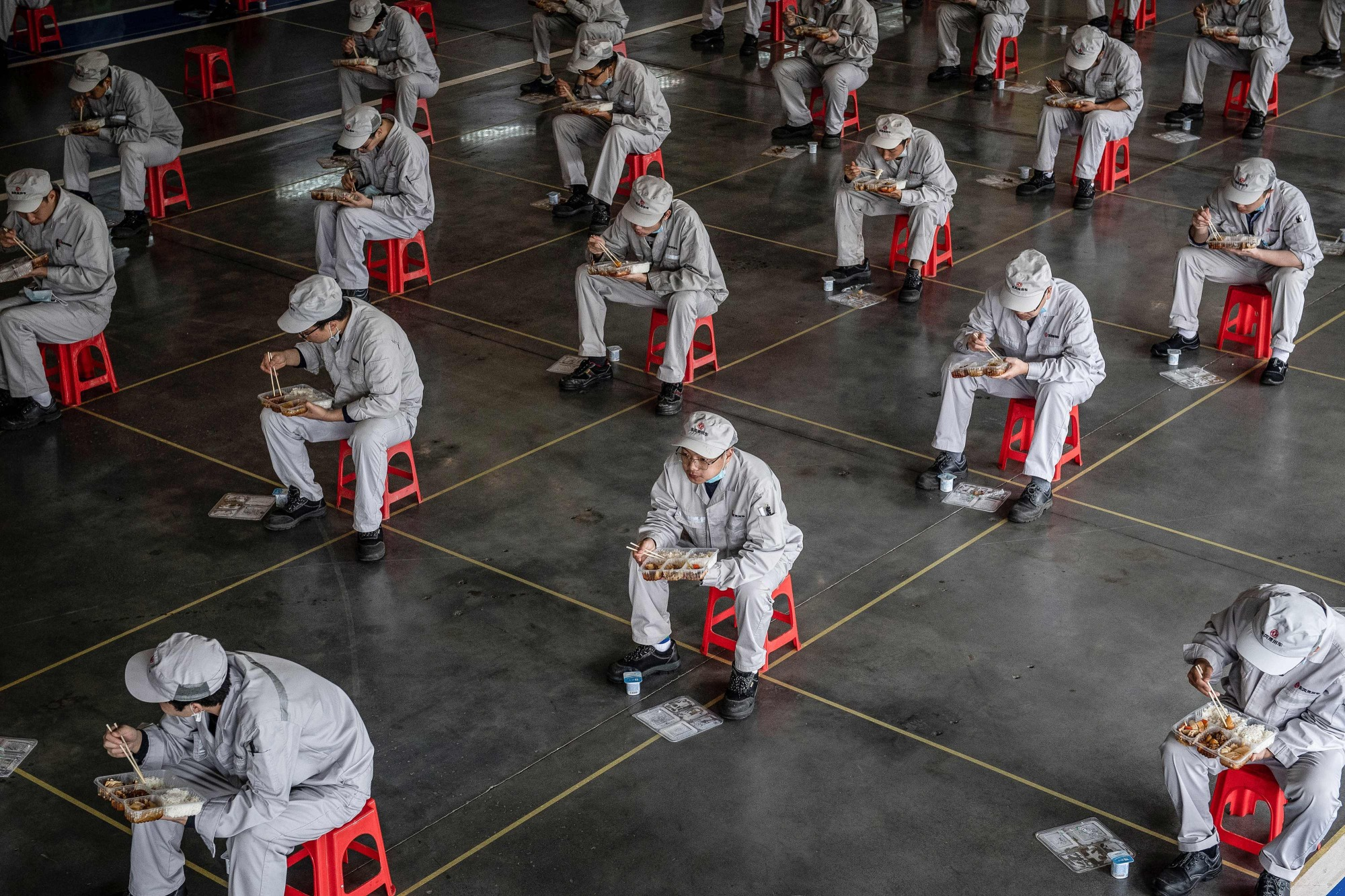 Employees eat during lunch break at a Dongfeng Honda auto plant in Wuhan, in China's central Hubei province, on Monday. | AFP-JIJI