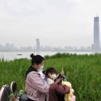 A mother and child at a park by the Yangtze River in Wuhan, China, on Thursday | REUTERS