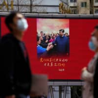 A screen showing an image of Chinese leader Xi Jinping is displayed after the city's emergency alert level for coronavirus disease was downgraded in Shanghai on Monday. | REUTERS